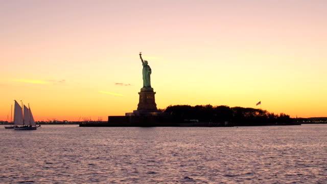 frihetsgudinnan-monumentet i new yorks hamn mot underbara eldig orange solnedgång - pink sunrise bildbanksvideor och videomaterial från bakom kulisserna
