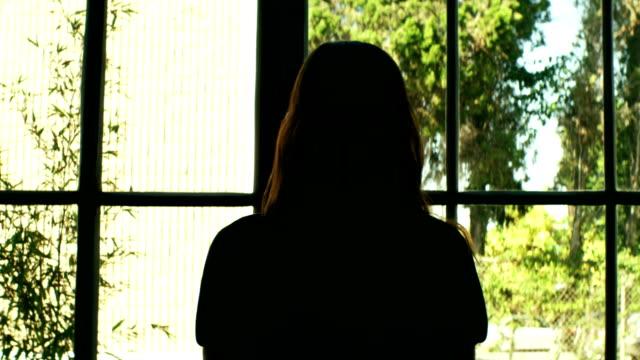 donna guardando fuori dalla finestra - dorso umano video stock e b–roll