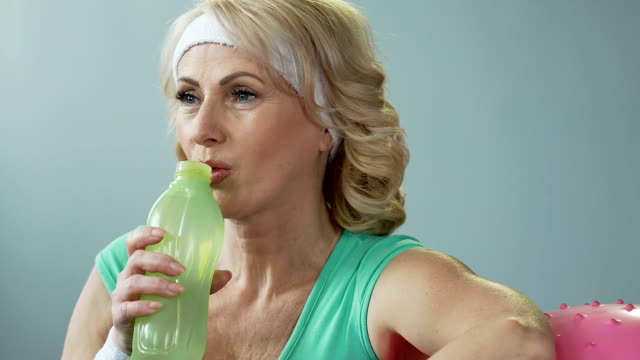 Lady of senior age leaning on fitness ball, drinking water and exhaling, results video