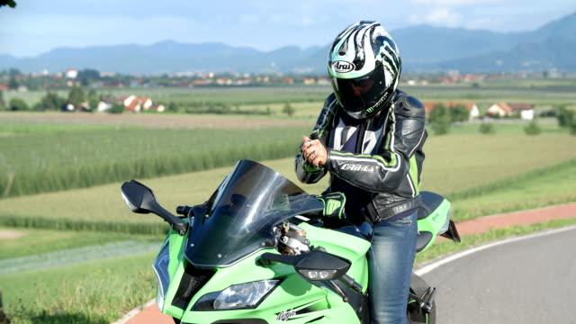 vídeos de stock e filmes b-roll de lady em um motard de tomar um sua capacete e as luvas - helmet motorbike