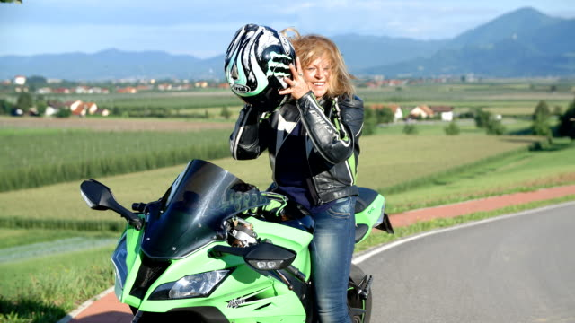 Lady on a motorcycle taking off her helmet and smiling video