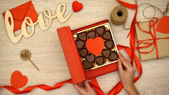 ハート形のチョコレート菓子は、媚薬とバレンタイン ギフト ボックスを開く女性 - バレンタイン チョコ点の映像素材/bロール