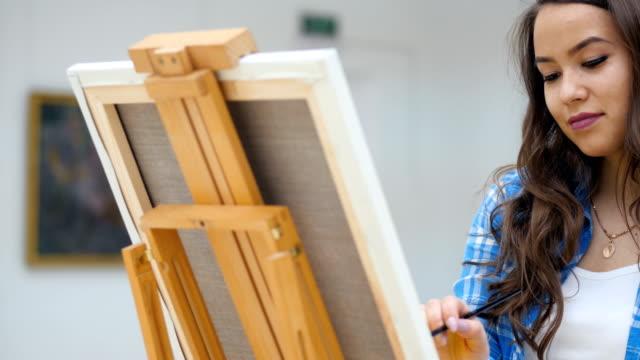 Lady painter at work. Steadicam. Close-up. 4K. video