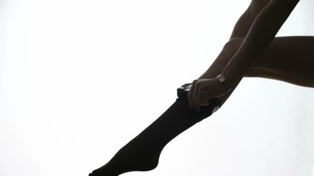 lady puts on stockings in silhouette - strumpbyxor bildbanksvideor och videomaterial från bakom kulisserna