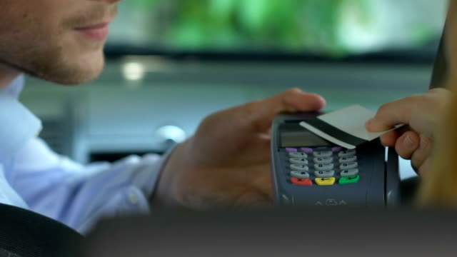 vídeos de stock e filmes b-roll de lady putting bank card to payment terminal making easy transaction for taxi ride - paying with card contactless