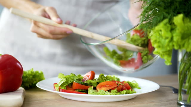 lady putting fresh salad on her plate, going to have lunch, healthy eating - insalata video stock e b–roll