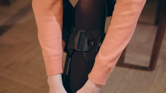 Lady Putting On Supportive Leg Brace video