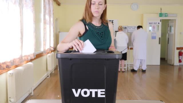 vidéos et rushes de 4k: lady mise aux voix dans les urnes lors des élections - voter au bureau de vote - picto urne