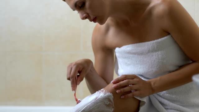 pani golenie nogi w łazience rano przed pracą, piękno i higiena - depilacja filmów i materiałów b-roll