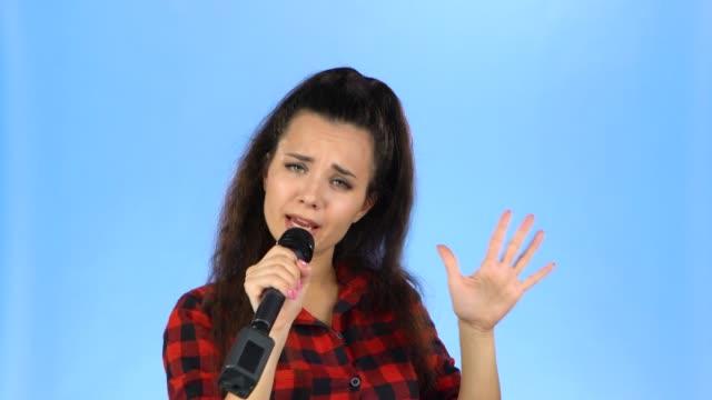 stockvideo's en b-roll-footage met lady zingt in een microfoon in een studio op een blauwe achtergrond - paardenstaart haar naar achteren