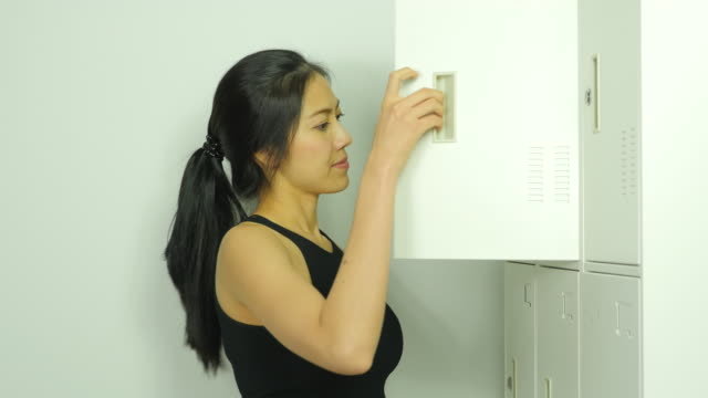 Lady take a break after exercise in locker room. Side view. Beautiful young lady take a break after exercise, get mobile phone and towel form locker. Side view. locker stock videos & royalty-free footage