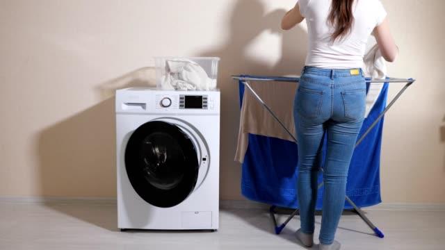 dame nimmt wäsche von waschmaschine und hängt auf rack - waschmaschine wand stock-videos und b-roll-filmmaterial