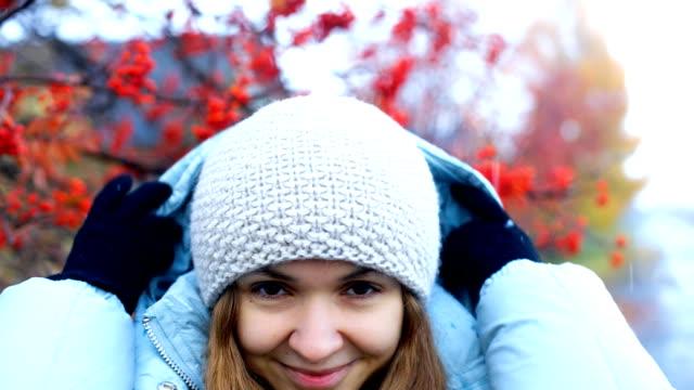 lady takes off warm jacket hood at rowan tree red berries