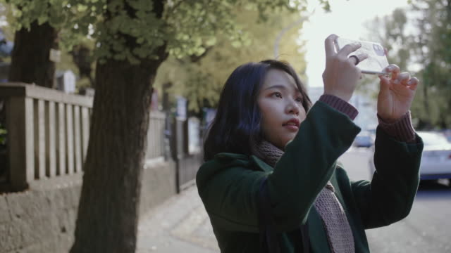 A Lady taking pictures of beautiful spring autumn public at the front of street.