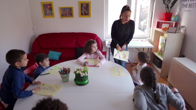 lehrerin im gespräch mit kindern im unterricht in privatschule - grundschule stock-videos und b-roll-filmmaterial