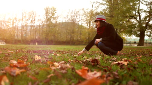 A lady teases her dog with an autumnal leave while walking outside video