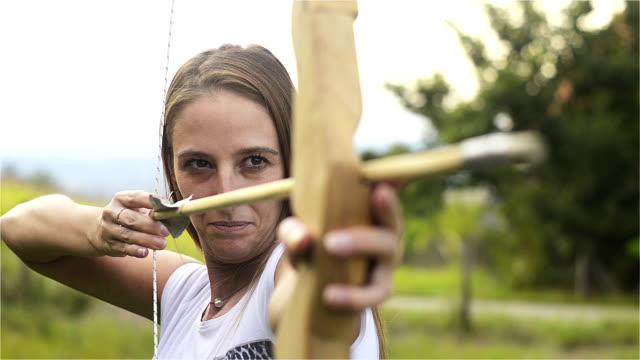 vidéos et rushes de lady resserre la flèche de l'arc et visez la cible orienté vers l'avant - tir à l'arc