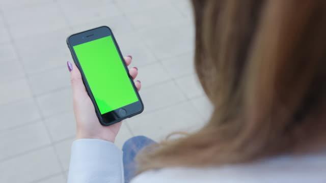 여자는 전화를 사용 하 여 녹색 화면 - hand holding phone 스톡 비디오 및 b-롤 화면