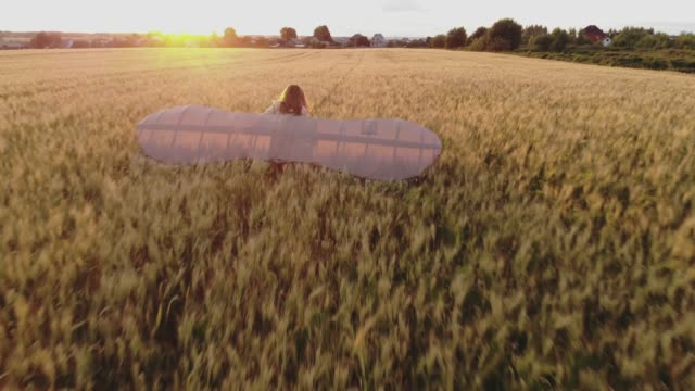 lady walks along field holding glider wings in evening video