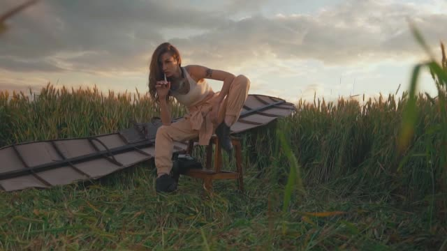 lady with long hair sits on stool against brown glider wings video