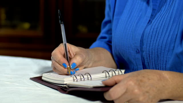 lady writing something on the diary, notebook, notepad video