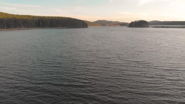 gün batımında göl. göl yüzeyinde uçuş, havadan çekim - full hd format stok videoları ve detay görüntü çekimi