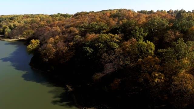 Lake background over blue sky, autumn forest - vídeo