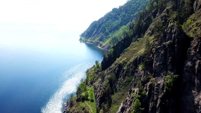 vídeos de stock e filmes b-roll de lake baikal oldest. railways russia siberia. mountains pine forest summer sun shines blue water. beautiful aerial follow above lake - irkutsk
