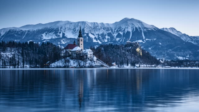 lake bled timelapse with bled island and bled castle during winter sunrise, slovenia - словения стоковые видео и кадры b-roll