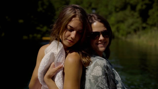lake enjoyment.two beautiful female friends enjoying a boat on their vacation. close up video
