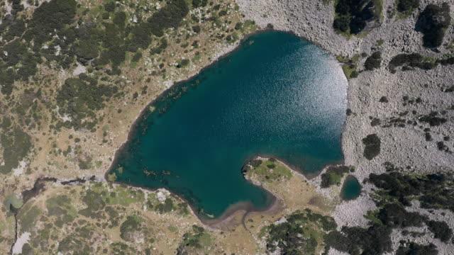 青い澄んだ水とドローンターンの表面の空中写真に太陽光の反射とクマの形をした山の湖。ピリン山、ブルガリアの夏の美しい山の風景。旅行 - 崖点の映像素材/bロール