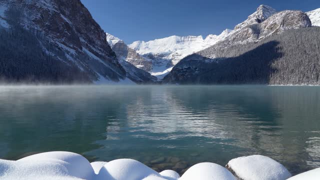 Lake Louise in early winter sunny day morning. Mist floating on turquoise color water surface