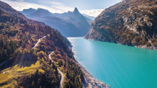 lake road turquoise mountains autumn zervreilasee switzerland aerial 4k - швейцарские альпы стоковые видео и кадры b-roll
