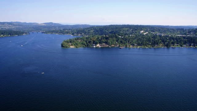 Lake Washington Sunny Day Real Estate Background Aerial Mercer Island helicopter shot flying lakeside with Interstate 90 bridge military private stock videos & royalty-free footage