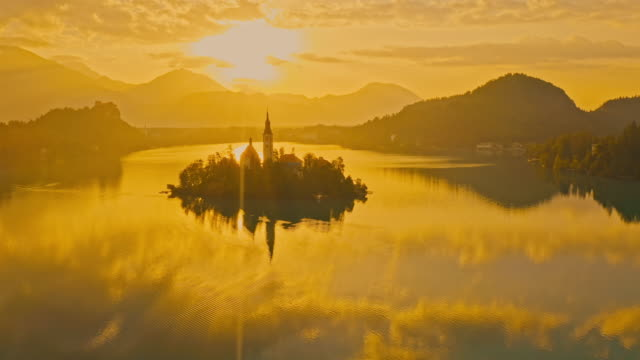 AERIAL WS Lake with island. Aerial view of Lake Bled with Bled Island at sunset / Slovenia church architecture stock videos & royalty-free footage