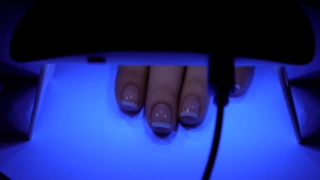 uv lampe gel polish maniküre-prozess in häuslichen bedingungen. - maniküre stock-videos und b-roll-filmmaterial