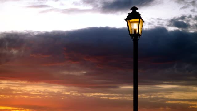 laterne. ein licht an der spitze eines hohen pfostens in der straße gegen den roten himmel. 4k - citylight stock-videos und b-roll-filmmaterial