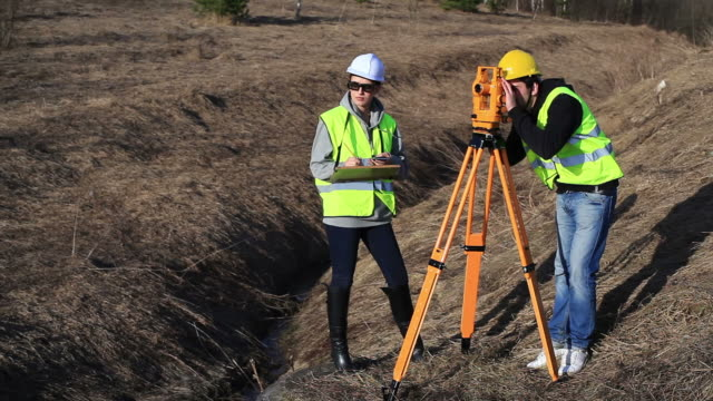 Land surveyors on construction site Land surveyors on construction site survey stock videos & royalty-free footage