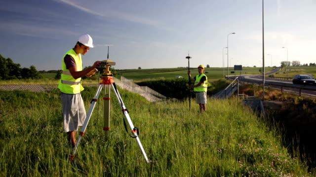 Land surveyors Land surveyors on construction site survey stock videos & royalty-free footage