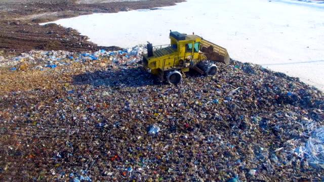 埋め立て地 buldozer はゴミ山の端に移動します。 - 豊富点の映像素材/bロール