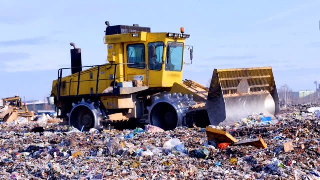 A landfill compactor working at landfill. Waste, garbage, dump, rubbish 4K. video