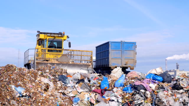 A landfill truck works near a garbage truck.
