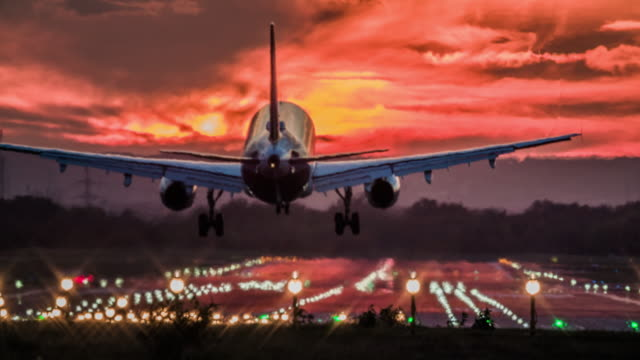 Landing airplane at sunset Airplane landing on an airport runway at sunset. Beautiful sky with dramatic red clouds. airport runway stock videos & royalty-free footage