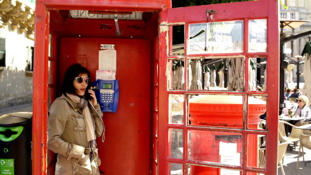 Landline phone is still in use,charming red telephone booth