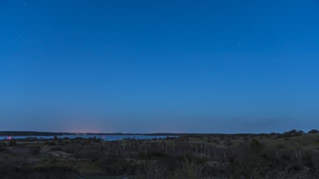 landskap dag till natt tid förfaller natthimlen med stjärnor och moln fångas på den kuperade halvön devin nära stralsund och ruegen med havet i bakgrunden - nightsky bildbanksvideor och videomaterial från bakom kulisserna