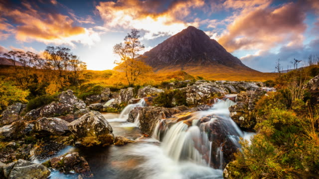 Landscape in Scotland - Buachaille Etive Mor - Tracking Time Lapse Time lapse tracking shot of a beautiful landscape in Scotland. Buachaille Etive Mor, know in Gaelic as The Great Herdsman of Etive, is pyramid shaped mountain. Watefall formed by river Etive in the foreground. Dramatic sunset sky with Colourful clouds. Scotland - UK scotland stock videos & royalty-free footage