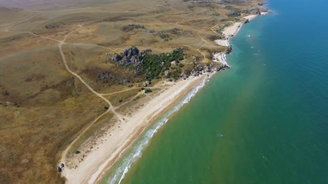 AERIAL: Landscape of hilly terrain with coastline of sea island video