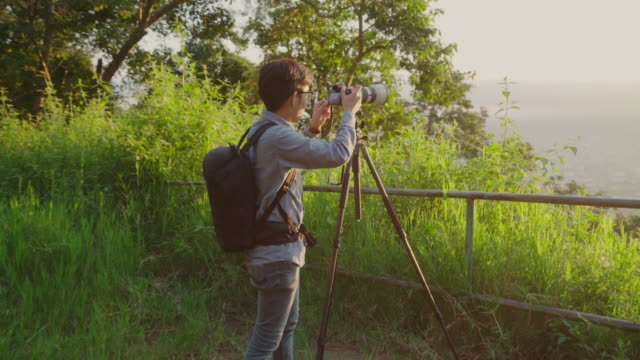 Landscape Photographer taking photos of sunrise in the morning video