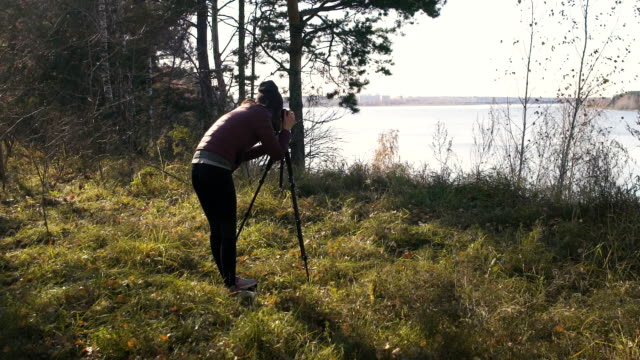 Landscape Photographer with Camera on a Tripod - Female artist taking travel photos in nature video