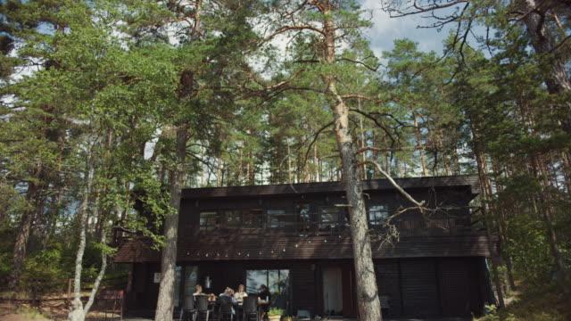 landschaftsaufnahme eines zweistöckigen black wooden cottage house in einem europäischen kiefernwald. junge freunde versammeln sich auf der terrasse. es ist ein warmer sonniger sommermorgen in romantischer atmosphäre in der natur. - landhaus stock-videos und b-roll-filmmaterial